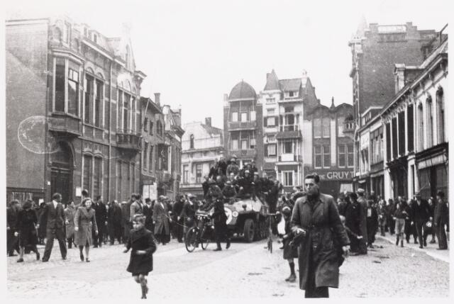 013296 - WO2 ; WOII ; Tweede Wereldoorlog. Bevrijding. Verkenningsvoertuig van de Royal Scots Fusiliers rijdt de Markt op. Voor het voertuig uit loopt de 9-jarige J. de Kok