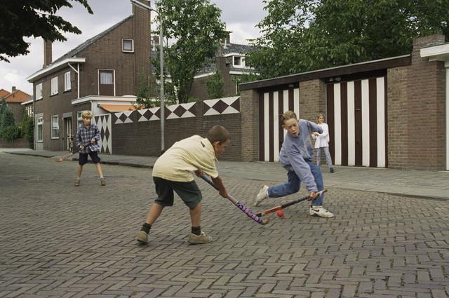 TLB023000938_003 - Kinderen spelen hockey op straat.
