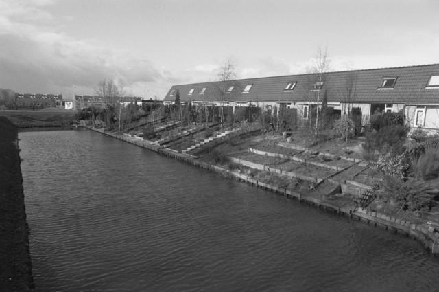 """TLB023000132_001 - Nieuwbouwhuizen met achtertuin aan een van de vele vijvers in nieuwbouwwijk. Foto gemaakt in kader Reeshof """"gezond beleid""""."""