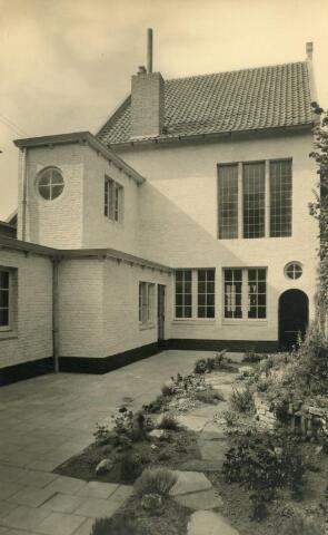 602007 - De achterzijde van de fotostudio en het atelier van hoffotograaf Leo van Beurden, gezien vanuit het pand Willem II-straat 39.  Op deze plaats stond eerst een koetshuis dat behoorde bij het pand aan de Willem II-straat en grensde aan de Wolstraat. Het koetshuis werd in 1937-1938 gesloopt en vervangen door een nieuw atelier/fotostudio. Architect Jos Bedaux was de ontwerper van dit pand. De voorzijde met hoofdingang grensde aan de Wolstraat, later Telexstraat.