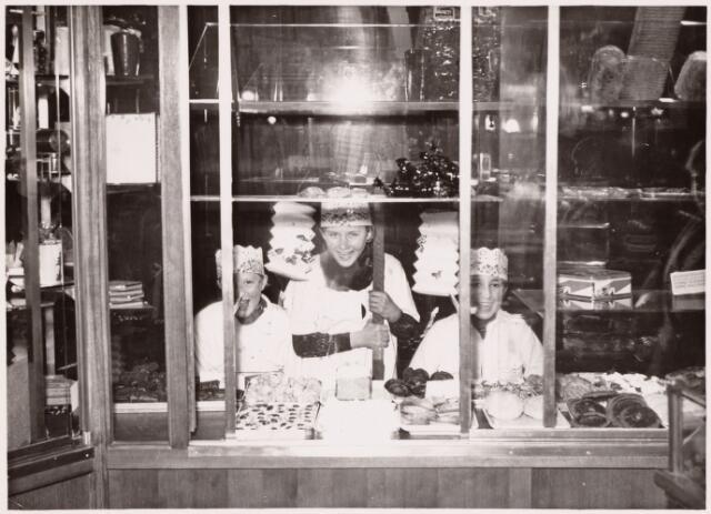 053117 - Foto afkomstig uit de collectie van de Tilburgse heemkundige Lambert G. de Wijs (1882-1949), die zich o.m. beijverde voor het behoud van tradities. Aan het Driekoningenzingen bewaren velen warme herinneringen. Deze foto van vrolijke Drie Koningen biedt tevens een inkijkje in de etalage van een Tilburgse patisserie anno 1934.