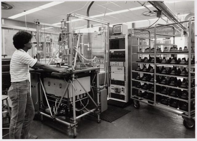 050137 - Volt, Noord, hal NB.  Produktie, Fabricage, Deflectie Units. Het meten met de Yama. De Yama was een apparaat dat eerst een deflectie-unit optimaal instelde en daarna, op 150 meetpunten, keek of de unit voldeed aan de kwaliteitseisen. De meetgegevens werden via een centrale computer verwerkt zodat een snelle terugkoppeling mogelijk was. Hier werden als meetinstrument nog 25 camera's gebruikt. Kort daarna werden die vervangen door lichtgevoelige cellen waardoor de meettijd enorm kon worden verkort. Yama is een afkorting van Yokering-Automatisch-Manipuleer-Aparaat. De yokering is de zwarte gesinterde metalen ring ( juist zichtbaar boven de rechter pols van de operator ) die destijds om elke deflectie unit zat en diende om het beeld optimaal in te stellen.