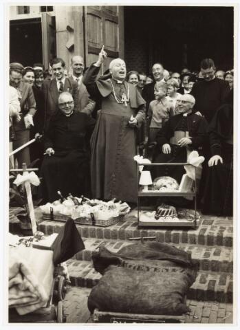 009735 - Bisschop W. Mutsaerts neemt geschenken in ontvangst bij de plechtige inzegening van de nieuwe parochiekerk O.L.Vr. altijd durende bijstand aan de Gasthuisring. zittend Llinks pastoor K. Janssens, staand: Bisschop W. Mutsaerts daarachter burgemeester baron van Voorst tot Voorst.