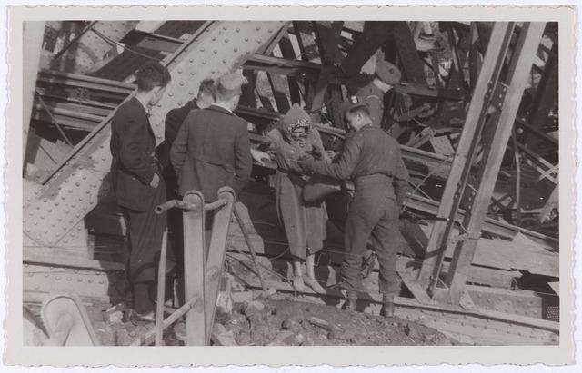 012350 - Tweede Wereldoorlog. Vernielingen. Een geallieerde soldaat helpt een vrouw via de vernielde spoorbrug naar de overkant van het Wilhelminakanaal