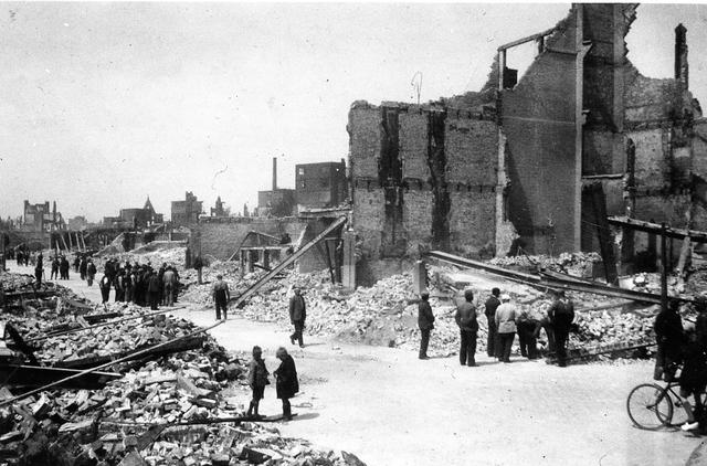 830010 - WO2; WOII; Tweede Wereldoorlog. Oorlogsjaren. 'Rotterdam zoals het was in mei 1940.' Groepjes mensen bekijken de puinhopen na het bombardement.