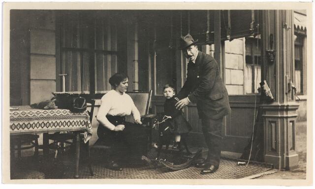 006712 - Heer en mevrouw Brouwers-van Waesberghe met kind op hobbelpaard op de veranda Begin 20ste eeuw