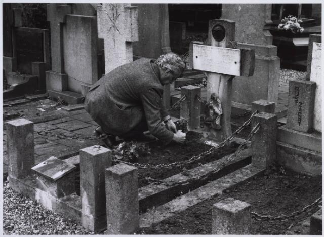 023078 - Een man legt bloemen op een graf op het kerkhof aan de St. Josephstraat