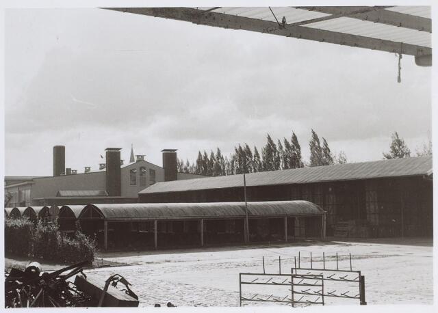 026082 - Textiel. Fietsenberging op het terrein van de Tilburgse katoenspinnerij TKT aan de Lovense Kanaaldijk. Op de achtergrond de torenspits van de Sacramentskerk