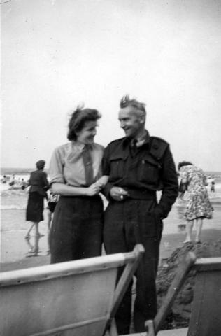 1709100 - De Tilburgse Harry Franken op het strand met een vrouw aan zijn arm. Tijdens de tweede wereldoorlog was hij tolk bij de Royal Air Force (R.A.F.). WOII.