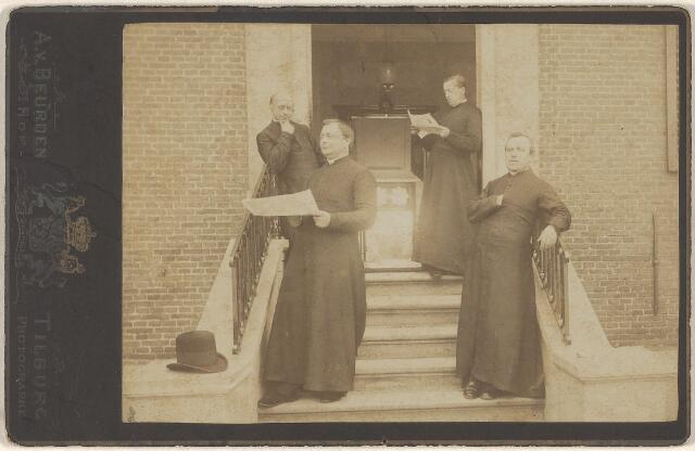 603810 - Pastoor en kapelaans van de parochie Goirke.   Johannes Baptista Bots werd geboren op 18-09-1838 te Helmond en tot priester gewijd in 1862. Datzelfde jaar werd hij als kapelaan benoemd in Udenhout. Drie jaar later, in 1865, werd kapelaan Bots overgeplaatst naar Den Bosch. Op 21 maart 1882 werd hij pastoor van de parochie Goirke te Tilburg. Hier zou hij meer dan 25 jaar als pastoor de parochie beheren. In 1908 werd Johannes B. Bots benoemd tot deken van het dekenaat Tilburg.   Links op de foto staat pastoor Bots, leunend op het traphek van de oude pastorie van het Goirke. Geheel rechts, lezend in de deuropening kapelaan Judocus Sprangers (Kaatsheuvel 1845-Grave 1926). Hij werd in 1879 kapelaan van de parochie Goirke en vertrok in 1892 als pastoor naar Nuland. Vooraan op de trap links staat Augustinus Henricus Maria Goossens (Diessen 1855-Meerveldhoven 1915). Hij kwam in 1887 vanuit Sint Michielsgestel om als kapelaan de parochie Goirke bij te staan. In 1902 vertrok Goossens uit Tilburg en werd pastoor te Meerveldhoven. Geheel rechts staat kapelaan Gerardus van den Boer (Someren 1851-Oss 1939). Hij was vanaf 1880 kapelaan van de parochie Goirke, werd in 1897 pastoor te Oss en werd uiteindelijk in 1906 benoemd tot deken van het dekenaat Oss.