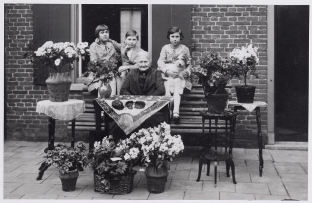045909 - Johanna (Sjo) Smulders, werd geboren te Tilburg op 12 maart 1860 en overleed te Goirle op 21 december 1951. Zij was een dochter van Petrus Smulders en Wilhelmina Michiels. Zij trouwde te Goirle op 16 februari 1887 met bakker Josephus Gerardus van Besouw, geboren te Oisterwijk op 28 september 1854 en overleden te Goirle op 23 mei 1918. De foto werd genoem t.g.v. haar 70e verjaardag achter haar huis aan de Kloosterstraat. Achter haar drie kleinkinderen- de kinderen van Jan van Besouw en Anna Vosters- van links naar rechts Cornelia Josephina Maria Anna (Corrie) van Besouw, geboren te Tilburg op 19 augustus 1919, Josephus Anselmus Petrus Johannes van Besouw, geboren te Tilburg op 17 januari 1921 en in 1954 vertrokken naar Ierland, en Johanna Cornelia Maria Anna (Jolanda) van Besouw, geboren te Velzen op 17 november 1917.