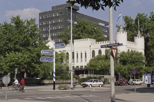 """TLB023000292_001 - Zicht op het oude en nieuwe stadhuis gezien van uit de Bisschop Zwijsenstraat. Het oude Paleis-Raadhuis werd gebouwd in opdracht van Koning Willem II en heeft verschilldende bestemmingen gehad, t.w. o.a. Paleis, Schoolgebouw en Gemeentehuis. Door ruimtegebrek werd besloten een nieuw Stadskantoor te bouwen, naar ontwerp van Architectenbureau Kraaijvanger. Het nieuwe kantoor, in de volksmond """"de Zwarte Doos"""" genoemd, werd in 1971 opgeleverd. Het oude en nieuwe stadhuis zijn middels een luchtbrug aan de noordelijke flank met elkaar verbonden."""