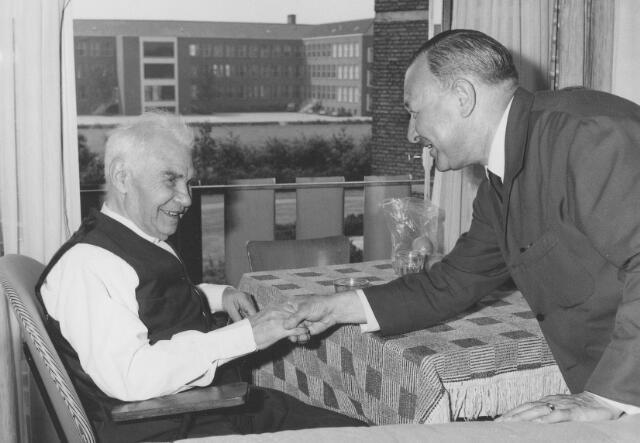 063940 - Norbert Mutsaerts directeur wollenstoffenfabriek A. & N. Mutsaerts op bezoek bij een oud werknemer in bejaardenhuis Vredeburcht.
