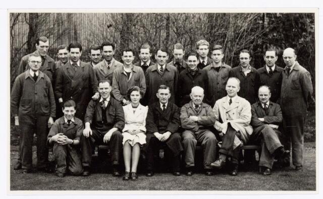 """039360 - Volt, Zuid. Technische Afdeling, Gereedschapmakerij. Een sub. afdeling van de Gereedschapmakerij was de afdeling """"Geux"""". Deze afdeling deed het onderhoud van de fabricagemachines uit de productieafdelingen. De opname is gemaakt omstreeks 1950 in de vroegere tuin van de Volt aan de Groenstraat waar later in 1962 het nieuwe hoofdkantoor werd geopend. Zittend v.l.n.r.: N.N, Konings, Jeanne Krijnen, Jan Hazendonk, Kees Overveld, Geux en Piet Haneveer.  Staande v.l.n.r.: N.N, Jan Willemsen, v.d. Hout, Bouwman, N.N, N.N, Pierre van Thielo, Albert Beukman, van Gestel, Frans Derksen, N.N, Doorakkers, Christ Pigmans, Chris Broos, Bosters en Rinus Laurijssen."""