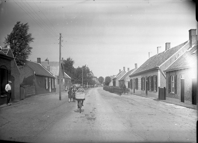 095040 - Dorpsbeelden Made. Straatgezicht in de jaren '30. Met enkele voetgangers en een jongen op de fiets.