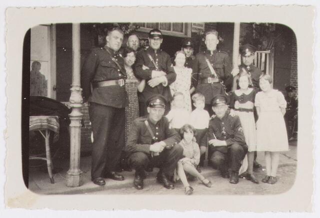 065094 - Politie. Een groep politieagenten met vrouw en kinderen poserend voor een café.