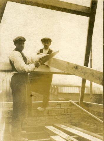 092772 - Timmerlieden in dienst van timmerfabriek J.G. Broeders aan de Groeseindstraat bezig met het stellen van dakspanten.