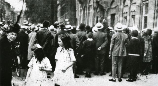065962 - Kermis. Op de hoek van de Spoorlaan bij de Heuvel proberen kermiskooplui hun waren te verkopen. Ze hebben een grote groep nieuwsgierige en kooplustige kermisbezoekers om zich heen verzameld.
