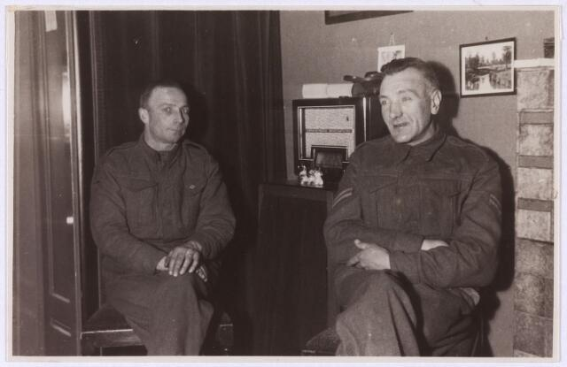 012897 - Tweede Wereldoorlog. Inkwartiering. Geallieerde militairen, de heren Hipsey en Woodhatle, in de huiskamer van hun gastfamilie