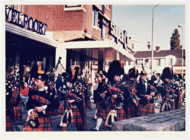 043373 - Op 27 oktober 1984 werden allerlei festiviteiten en herdenkingen gehouden b.g.v. 'Tilburg 40 jaar bevrijd'. Hier trekt een groep militaire wagens van de organisatie 'Keep them rolling'. Hier een piperband bij de achterzijde van de Heuvelpoort Piusplein.