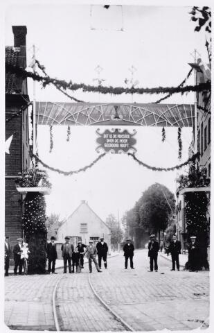 046623 - Ereboog bij de ingang van de Tilburgseweg ter gelegenheid van het zilveren priesterfeest van pastoor Peters. Links de zijgevel van het nonnenklooster. Op de achtergrond het woonhuis van de familie Snels-Klijs.