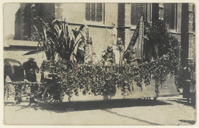 """89107 - De jaarlijkse Kindsheidsoptocht in Terheijden omstreeks 1920 met ook een H. Hartbeeld op een boerenwagen. Op het lint staat de tekst: """"IK ZAL DE PLAATSEN ZEGENEN, WAAR MIJN BEELD VEREERD WORDT"""". In 1923 kreeg Terheijden een groot H. Hartbeeld en dat werd feestelijk ingewijd op het Zandpleintje, nu Dorpsplein, en geplaatst bij de kerk."""