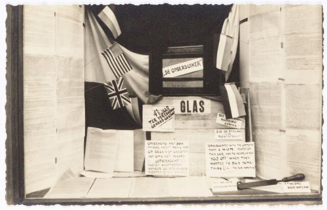 """049834 - In een van de etalages van De Vet aan de Poststraat werd na de bevrijding de kist tentoongesteld, waarin het radiotoestel, boven op de kist, verborgen zat. Links en recht getypte nieuwsbulletins, uitgezonden door radio Oranje. Voor de kist het verhaal over de """"luistervinken"""" in het Engels en Nederlands.De foto is een reconstructie van de situatie tijdens de Tweede Wereldoorlog."""