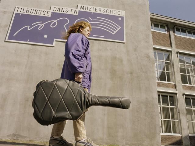 """TLB023000171_001 - Student met gitaar voor het gebouw van de Tilburgse Dans- en Muziekschool destijds gevestigd in de voormalige Wollenstoffenfabriek George Dröge NV. Foto genomen in kader """"SPB / BouwRai"""" ter promotie van het """"Samenwerkingsverband Praktijkopleiding Bouw"""" en de tweejaarlijkse bouwmaterialenbeurs in de Amsterdamse RAI."""