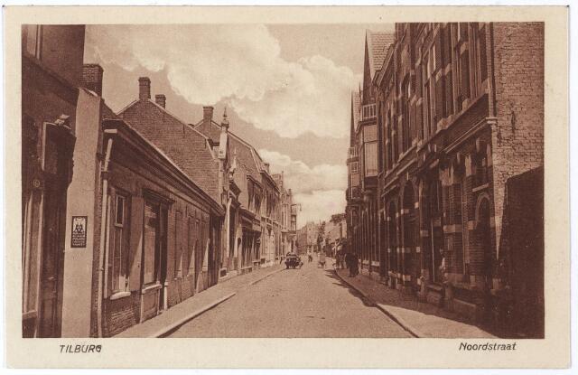 001726 - Noordstraat in noordwestelijke richting. De lage huizen links zijn v.l.n.r. de panden Noordstraat nrs. 117 en 115, voorheen M 853 en M 852. In het eerste pandje woonde rond 1900 boekdrukker W. van Eijk en daarna boekdrukker Arnoldus J. de Bont, die ook ansichtkaarten uitgaf. De Bont, getrouwd met Wilhelmina Petronella Bergmans verhuisde in 1922 naar de Tuinstraat. Op nr. 115 woonde vrachtrijder Petrus Fr. Claassen, getrouwd met Maria Clotilde Adriana v.d. Kerkhof. Hij overleed er op 16.3.1925. Zijn zoon, Paulis Fr.M. Claassen, expediteur, trouwde op 24.10.1922 met Francisca Adriana Berkelmans en dit echtpaar betrok het pand nr. 117, vanaf oktober 1925 tot 1934 woonde er zijn broer Florentinus F.L.M. Claassen, aanvankelijk wagenmaker en chauffeur. Huisnummer 117 werd bedrijfsruimte. Vanaf 1926 heette het bedrijf Gebroeders Claassen, maar in 1934 gingen de broers hun eigen weg. F. Claassen werd eigenaar van  Expeditie en Transportbedrijf F. Claassen aan de Boomstraat, P. Claassen werd directeur van Expeditiebedrijf P.F. Claassen aan de Noordstraat, later aan de Lambert de Wijsstraat. Geheel links de voordeur van het pand Noordstraat 119. Hier woonde Augustinus A. van Os, handelaar in kerkartikelen. Op de zijgevel van het huis van Claassen zien we een reclamebordje van Van Os, met een wapen waarop drie ossenkoppen. Aan de rechtzijde van de straat de panden Noordstraat 94, volgens de gevelsteen gebouwd in 1903 en nummer 96. Op nr. 94 woonde groentekoopman Th.J. Verhaaren geboren te Grave en overleden te Tilburg op 28.7.1922. Zijn weduwe verhuisde op 18.2.1929 naar Noordstraat 14b. Op nr. 96 woonde Franciscus Alphonsus van Vlerken uit Bergeijk. Hij was broodbakker.