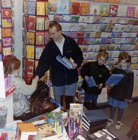 1237_001_005_004 - De prijsuitreiking van een kleurwedstrijd in een kantoorboekhandel aan de Korvelseweg in december 2001. De winkelier feliciteert de kinderen en overhandigd de prijzen in zijn winkel. De wedstrijd was een initiatief van winkeliersvereniging Korvel Vooruit.