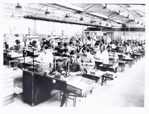 038536 - Volt. Zuid. Fabricage. Productie. Voorbewerking van meervoudige condensatoren in 1933 in shedbouw C aan de Voltstraat (toen nog Nieuwe Goirleseweg). De eerste man op de achterste rij links, pal voor de tweede elektrische schakelkast van links is Dhr.André van Iersel. Hij werkte ruim 20 jaar in deze afdeling als controleur. Foto uit gedenkboek afscheid van Dhr. Anninga directeur.
