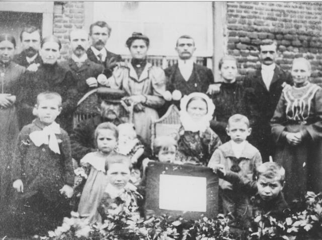 064498 - Familie Smulders-de Brouwer. Zittend in de rieten stoelen wever Peter Smulders, geboren te Tilburg op 25 januari 1841 zoon van Joannes Smulders en Joanna Smolders, en Willebrordina de Brouwer, geboren te Diessen op 7 september 1843, dochter van Willebrordus de Brouwer en Petronella Berkvens. Het paar trouwde te Tilburg op 10 oktober 1867 en woonde aldaar aan het Groeseind. Op de achterste rij hun kinderen en schoonkinderen v.l.n.r.: Johanna Maria Smulders geboren te Tilburg op 25 november 1871, haar man Hendrikus Cornelis (Harrie) Staps, met wie zij te Tilburg op 15 januari 1896 trouwde, Petronella van der Zanden, die op 29 april 1896 te Tilburg trouwde met de volgende persoon, Johannes Cornelis (Jan) Smulders, geboren te Tilburg op 1 augustus 1868, Joannes Josephus (Jan) van Huykelom, hij trouwde te Tilburg op 4 juli 1900 met de vrouw naast hem, Petronella Catharina Smulders, geboren te Tilburg op 25 juni 1880, vervolgens Adrianus Josephus Smulders geboren te Tilburg op 3 oktober 1877, Anna Maria (Anna) Smulders geboren te Tilburg op 24 september 1882 (weduwe van Engelbertus Stokkermans, later hertrouwd met Johannes Jacobus Leenhouwers), Wilhelmus Josephus (Willem) Smulders, geboren te Tilburg op 8 maart 1875 en een zekere Anna. Op de voorgrond de kleinkinderen v.l.n.r.: Harrie van Huykelom, Wies van Huykelom, voor haar Piet Smulders, op schoot bij opa Tonia Stokkermans, achter het bord  Jo Smulders, naast zijn grootmoeder Jan Smulders en tenslotte Toon Staps.