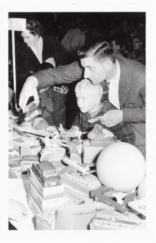038865 - Volt. Zuid. Sport en ontspanning. Viering Sint Nicolaas voor de kinderen van het personeel in 1960. Op de foto Sjef van den Hout met zoon bij het uitkiezen van een cadeautje. Sinterklaas. St. Nicolaas