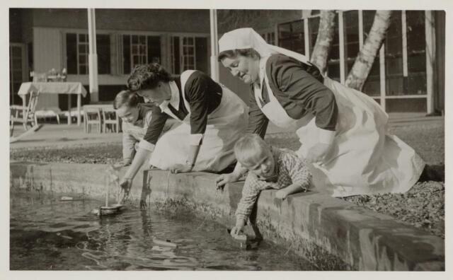 046363 - Medisch kinderdagverblijf Kleuterheil. Verplegend personeel met kleuters spelend met bootjes in de vijver.