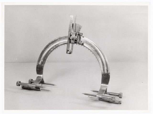 038590 - Volt. Zuid. Opleidingen. Justeerapparaat ca. 1955/1960, gemaakt door leerlingen van de vakliedenopleiding op verzoek van dr.Grood, destijds neurochirurg aan het St. Elisabeth ziekenhuis. Het apparaat werd gebruikt bij operaties in het hoofd. De pennen links en rechts dienden om het apparaat op het hoofd vast te klemmen. Het gedeelte bovenaande cirkel was verschuifbaar langs die cirkel, om zodoende de juiste invalshoek te bepalen. Bovendien was de hoogte instelbaar zodat een zekere (boor?) diepte kon worden ingesteld.