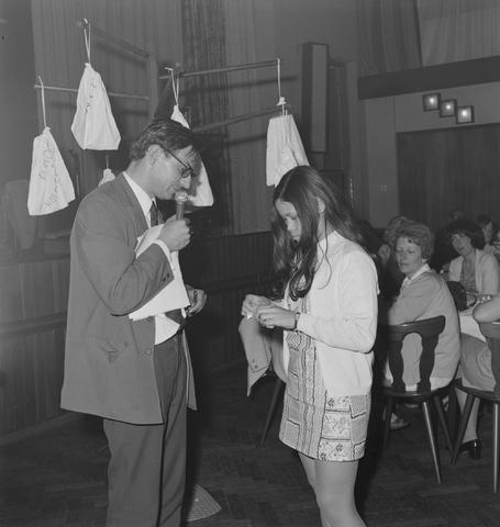 1237_004_102-2_004 - Man met microfoon en jonge vrouw tijdens een personeelsfeest van wolfabriek 3 Suisses.
