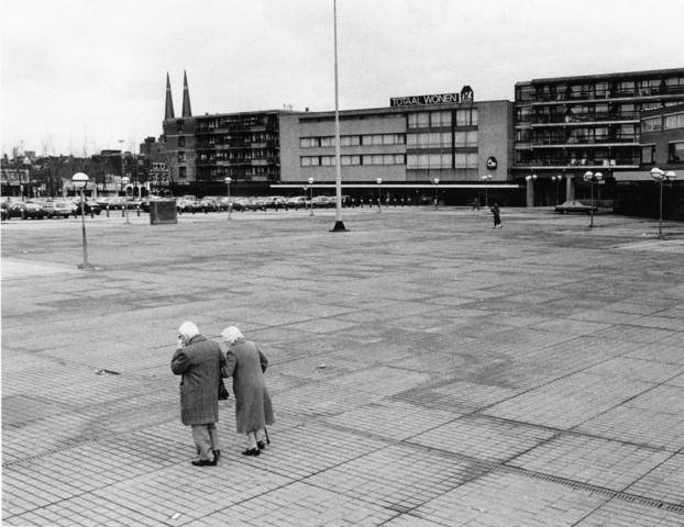 1238_F0384 - Twee oudere mensen lopen over het Piusplein. Op de achtergrond: De Heuvelse kerk.
