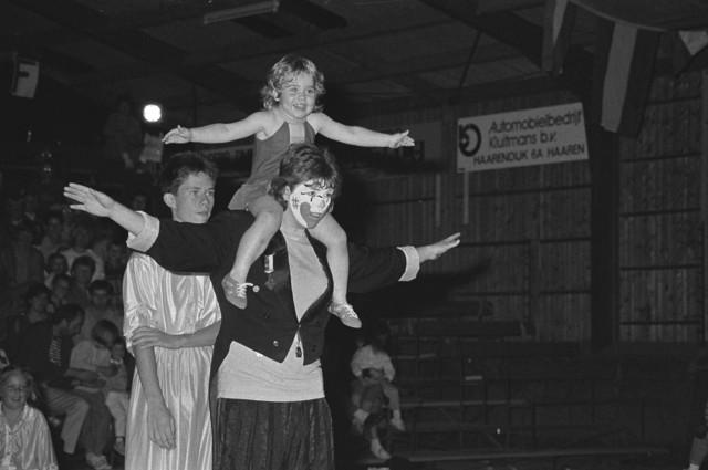 TLB023002532_001 - Optreden van een clown, met een meisje op zijn schouders, de jongen achter de clown staat er voor de veiligheid van het kleine meisje