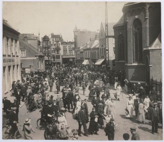 027707 - Markt 2-20 (rechts), tussen Hotel De Gouden Zwaan en de kerk van het Heike, bij het uitgaan van de kerk op Koninginnedag.