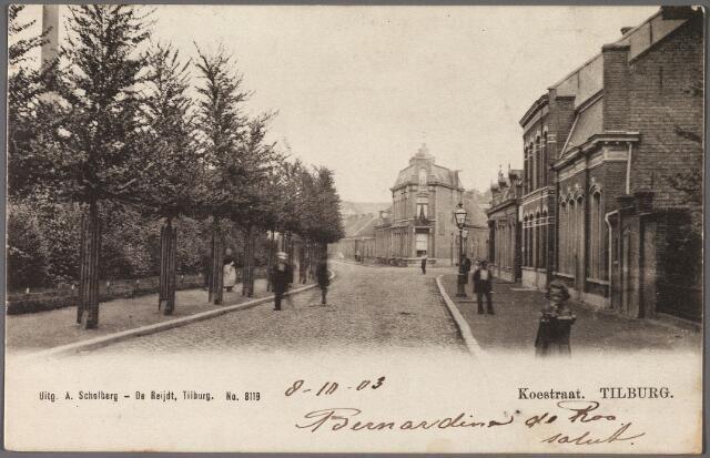 010491 - Koestraat met links achter de bomen de werkplaatsen van de N.S. Op de achtergrond bij het hoekhuis de splitsing met de Enschotsestraat.  Ter plaatse heet het nu N.S.plein.