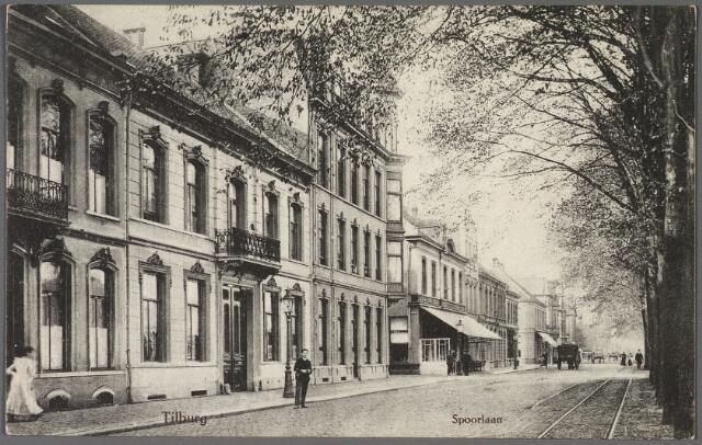 010677 - Spoorlaan richting Noordhoek. In het midden het pand Spoorlaan 112, nu 406/408 op de hoek van de Langestraat. Links daarvan de panden M 1539 en 1540 vanaf 1910 de huisnummers 108 en 110.  Nummer 108 werd rond 1900 bewoond door fabrikant G.C. Thijssen, op nummer 110 woonde rond 1900 de weduwe Lommen-Bulterijs met haar zonen die manufacturier waren. Rond 1910 woonde in dit pand wijnhandelaar Bernardus J.M. Verbunt, getrouwd met Louisa J.M. Janssens. Verbunt verhuisde in 1911 naar de Nieuwlandstraat. Dit pand is daarna gesloopt. In 1915 werd er onder architectuur van Francois de Beer de Zuid-Nederlandsche Handelsbank gebouwd. Op nummer 108 woonde vanaf 16.12.1921 Charles Pierre Alexander Gimbrere, winkelier, 'koopman in dameshoeden'. Hij was getrouwd met Franciska Vanwest uit St. Truiden. Rechts de tramrails van de lijn Tilburg-Goirle-Hilvarenbeek-Esbeek.