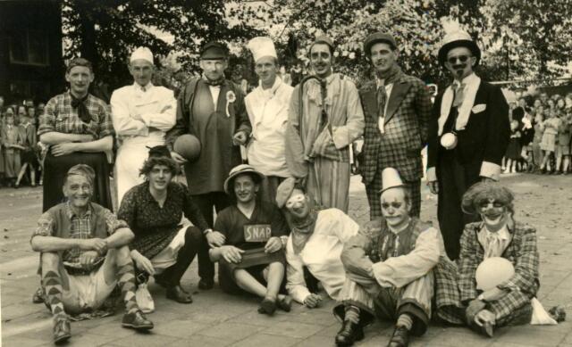 """602235 - Verkleed voetbalteam voor een feest georganiseerd door de winkeliersvereniging Korvel Vooruit t.g.v. de asfaltering van de Korvelseweg. Zittend geheel rechts Kees de Bakker. Hij dreef aan de Korvelseweg samen met zijn vrouw een winkel in touw en papier. Voorheen was de winkel van zijn schoonouders Robben en stond de zaak bekend als """"Robbeke Touw"""".  Zittend derde van links Frans van Zantbeek als juffrouw Snap uit de Snip en Snap Revue.  Links van hem juffrouw Snip. Van Zantbeek had een winkel in haarden, kachels en huishoudelijke artikelen, eerst aan de Zomerstraat, later aan de Korvelseweg."""