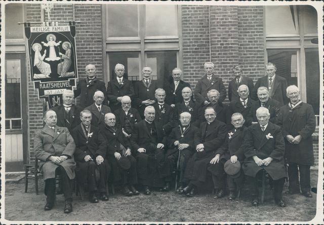 """651449 - Aartsbroederschap van de Heilige Familie te Kaatsheuvel. De broederschap werd opgericht in Luik op 7 april 1848 door kapitein Henri Belletable. Het is een lekenorganisatie binnen de Rooms Katholieke kerk; de orde organiseerde vooral werklieden en hielden wekelijks bidstonden en hield ook andere vieringen. Het doel was: """"de Heilige Familie vereren en aan katholieken van beider seksen, van alle leeftijden en standen een heilzame gelegenheid te verschaffen, om met zekerheid de weg der deug te bewandelen"""". In 1951 had de orde 700.000 leden over de hele wereld, maar in de jaren 60 implodeerde de orde volledig.  Op de eerste rij zitten van links naar rechts: Jan Jansen, Dirk Snoeren, Peter Klijn, Deken Van den Brekel (pastoor van de St. Jansparochie van 1934 - 1954), Cees (Ciske) Roestenberg, kapelaan Van den Heuvel (directeur van de orde), Dirk Laros en Gerrit de Wit. Op de tweede rij staan: Jan Kemmeren, Janus van Iersel, Helmus Westerveld, Graad Horrevoorts, Jan Brocken, Nieske Vastré, Narus Oerlemans, Wout Couwenberg en Jan Donders. Op de derde rij staan Martien van Riel, Gijs Laros, Jan Morval, Jan van Wezenbeek, Thijs Soeterboek, Dorus Hendriks en Tinus Broeders. Op de heren Roestenberg en Jansen na waren allen gouden en diamanten jubilarissen. Links achter staat het vaandel van de Kaatsheuvelse broederschap.  Het gebouw waarvoor zij staan is de oostgevel van het patronaat bij de St. Janskerk in Kaatsheuvel ter gelegenheid van het 75-jarig bestaan van het Aartsbroederschap van de Heilige Familie in Kaatsheuvel. De St. Janskerk, parochie Heilige Willibrord, is een kleine 100 jaar oud. De kerk is gebouwd als neogotisch ontwerp door de Tilburgse architect Cornelis van Hoof (1861-1952), kostte fl. 168.000,00 en was de op één na grootste kerk in Brabant. De kerk werd op 5 juli 1913 in gebruik genomen."""
