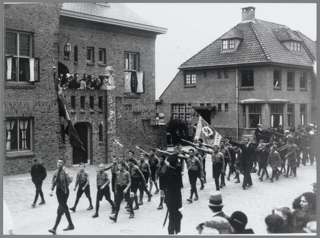 88794 - Twaalf en half jarig jubileum burgemeester W.A.J. van der Meulen met rechts de ambtswoning. Hier passeert de R.K.J.... uit Langeweg met vaandel.