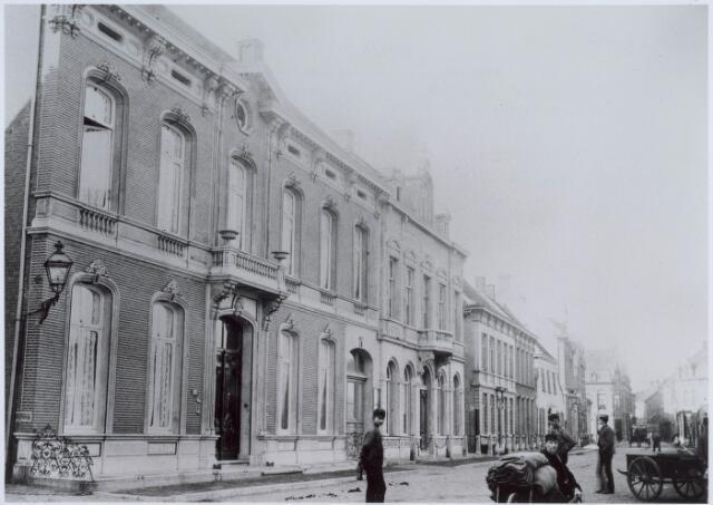 021121 - Zuidelijk deel van de Heuvel omstreeks 1892, toen het nog Heuvelbocht heette. Links, op de hoek met de Damsstraat, het pand van de familie Taminiau. Rechts op de voorgrond een man die stukken vervoerd op een kruiwagen, waarschijnlijk voor de firma Van den Bergh & Krabbendam (BeKa)