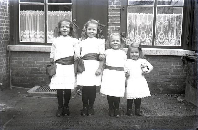 651604 - Vier kinderen in witte jurken met zwarte kousen en schoentjes. De Bont. 1914-1945.