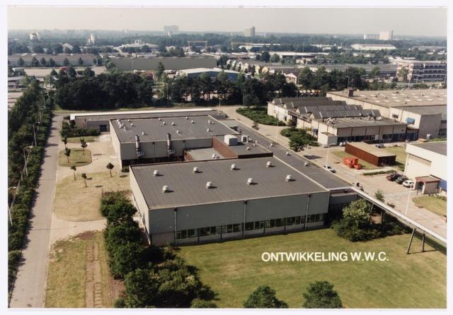 038942 - Volt Noord. In de 2e helft van 1985 kwam het W.W.C.-Laboratorium, een deel van het vroegere A.T.-Lab., vanuit Eindhoven naar Volt. De afkorting W.W.C. staat voor Wire Wound Components ofwel draadgewonden producten. Ontwikkeld werden daar o.a. spoelen, transformatoren en lijntransformatoren (L.O.T.) ook wel lijntrafo´s genoemd.  Met die komst werd fysiek het hoogste punt van Volt bereikt. Op 15 juni 1985 werd namelijk een mast van 45 meter hoogte geplaatst voor de ontvangst van radio- en televisiesignalen ten behoeve van de ontwikkeling W.W.C.  Deze foto is genomen vanuit die mast in zuidelijke richting en laat de gebouwen NS zien die bij W.W.C. in gebruik waren.