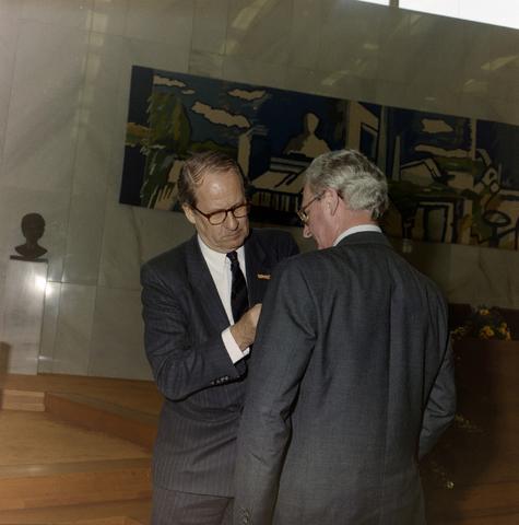1237_012_970-1_010 - Koninklijke onderscheiding. Lintje. Lintjesregen bij de Gemeente Tilburg in april 1992. Burgemeester Gerrit Brokx spelt een lintje op in de vergaderzaal van Gemeente Tilburg.