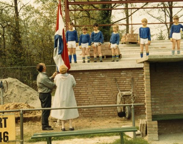 800076 - Voetbal. Bouw van de tribune van voetbalvereniging Taxandria in Oisterwijk. Het hoogste punt is bereikt. De vlag wordt gehesen door wethouder Greet Ermen.