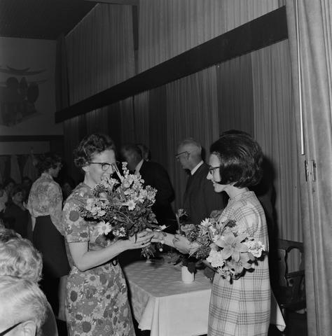 1237_004_102-1_003 - Er worden bloemen uitgereikt aan een mevrouw in een bloemetjesjurk tijdens een personeelsfeest van wolfabriek 3 Suisses.